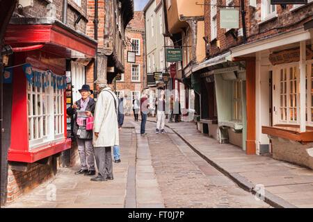 Pareja senior de compras en The Shambles, York, North Yorkshire, Inglaterra, Reino Unido ligero desenfoque de movimiento en la cara de mujer en tallas grandes.