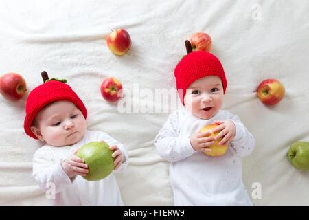 Dos lindos bebés acostado en sombreros en Manta suave con manzanas