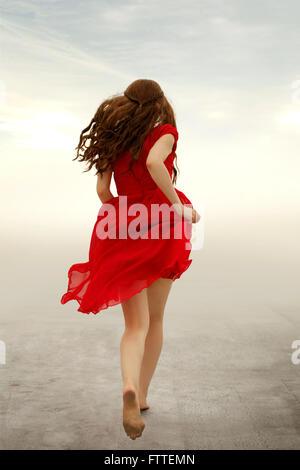Mujer de vestido rojo huyendo
