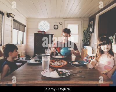 Padre con hijos almorzando en casa