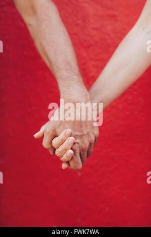Cerca de pareja tomados de las manos contra la pared roja. Disparo vertical de amar a un hombre y una mujer cogidos de la mano.