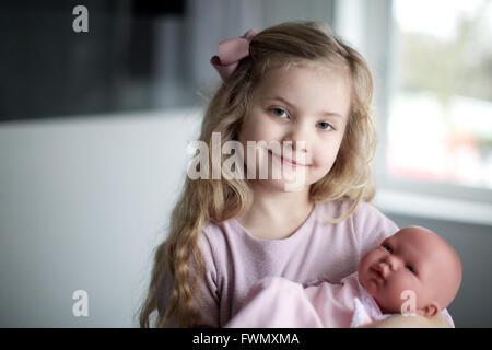 Retrato de chica con baby doll envuelta en una toalla. Kid, de felicidad, de juguete, el cuidado de los niños.