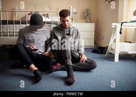 Dos estudiantes varones en dormitorio Comprobar mensajes en teléfonos móviles Foto de stock