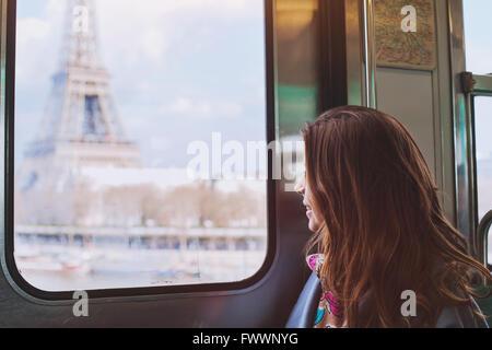 Turismo en busca de la Torre Eiffel a través de la ventana del metro de París, de visita en Francia chica sonriente
