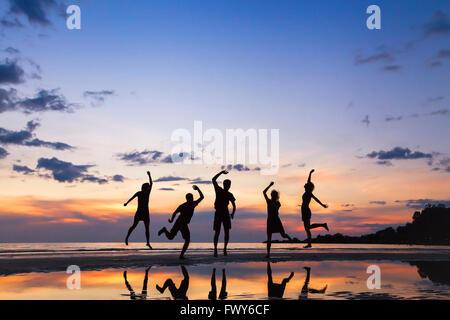Grupo de personas saltando por la playa al atardecer, silueta de amigos divirtiéndonos juntos