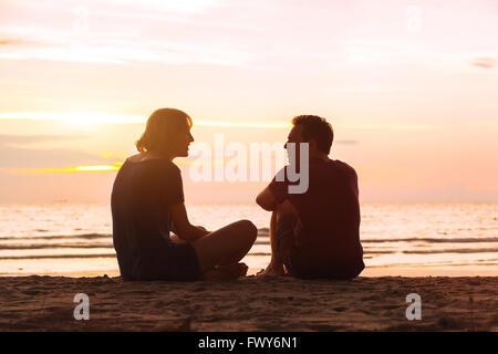 El hombre y la mujer en la playa al atardecer, pareja joven hablando cerca del mar, citas o concepto de amistad Foto de stock