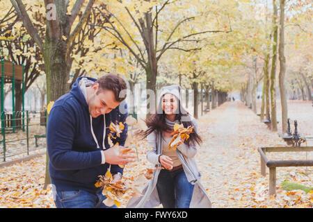 Joven pareja feliz jugando y riendo juntos en otoño park