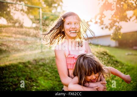 Dos lindas chicas que se divierten fuera en el jardín de verano Foto de stock