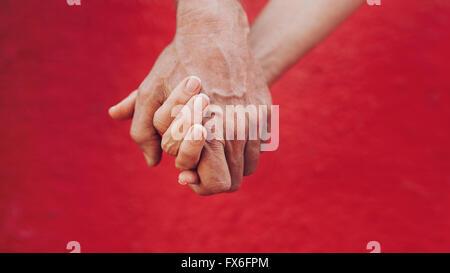 Cerca de un hombre y una mujer cogidos de la mano contra el fondo rojo. Afectuosa pareja cogidos de la mano.