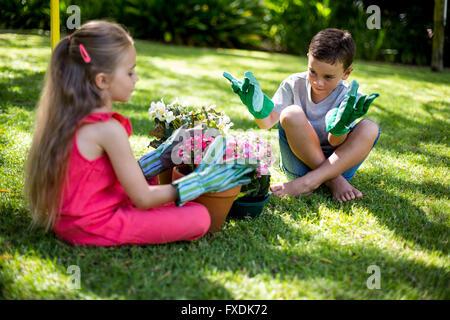 Hermanos con macetas sentado en el patio
