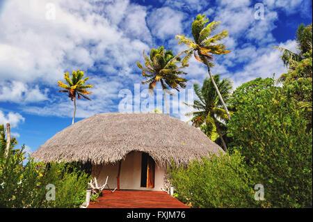 Tikehau, el atolón de las Islas Tuamotu, Polinesia. Un eco resort en medio de palmeras verdes con una bonita postal sky