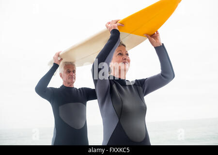 Las parejas ancianas en llevar traje de neopreno, tablas de surf sobre la cabeza
