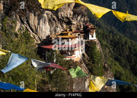 Vista entre banderas de oración a Tiger's Nest (Monasterio de Taktshang), encaramado sobre un acantilado cerca de Paro, Bhután