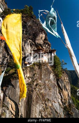 Ver a través de la oración banderas a Tiger's Nest (Monasterio de Taktshang), encaramado sobre un acantilado cerca de Paro, Bhután
