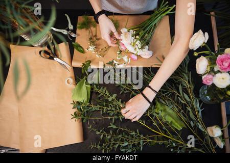 Vista superior de las manos de la joven florista creando ramo de flores en la mesa negra