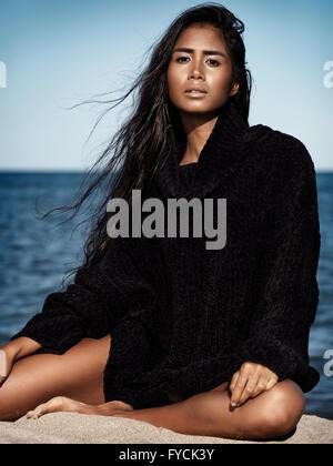Mujer joven vistiendo un suéter negro sentado en la arena en la playa. Foto de stock