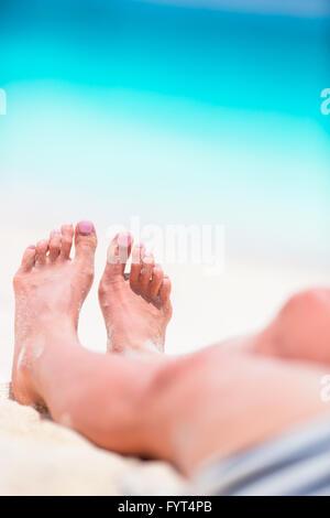 Los pies femeninos en la playa de arena blanca en el agua poco profunda
