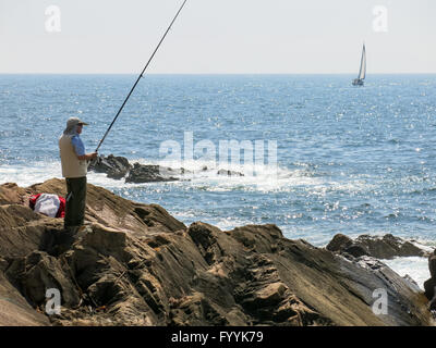 Pescador pesca en el Océano Atlántico y el velero navegando en el mar frente a la costa de Foz cerca de Porto, Portugal