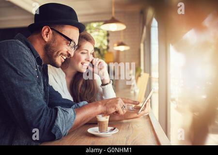 Sonriente joven pareja en una cafetería con equipo con pantalla táctil. El hombre y la mujer joven en un restaurante mirando tableta digital Foto de stock