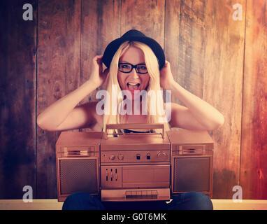 Una rubia hipster chica con gafas es escuchar una vendimia oro boombox radio con un altavoz para un concepto de entretenimiento musical Foto de stock