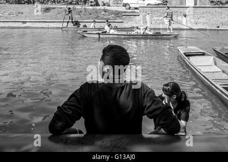 Un joven hombre espera guía a lo largo de la orilla del río Cam en Cambridge, Cambridgeshire en mayo en un soleado día de sol caliente