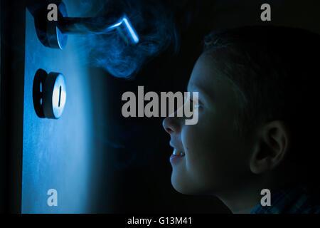 Niño en una habitación oscura, mirando en el resplandor de una linterna a través de un orificio en el cual el humo sube.