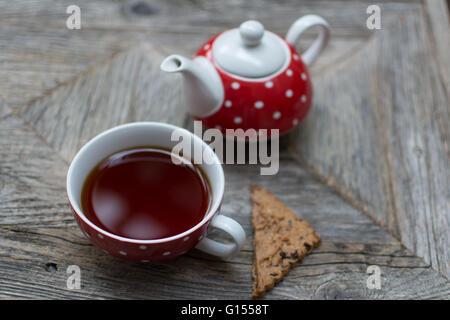 Té de Rooibos con una galleta de té y una tetera en el fondo, todo sobre una tabla de madera recuperados.