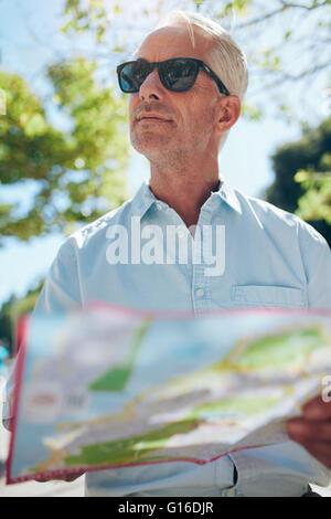 Primer plano de un hombre maduro, con un mapa mientras está parado afuera de la ciudad en un día de verano. Holding turístico un mapa de la ciudad y loo