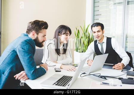 Joven Empresaria y hombres mirando un portátil en mesa de juntas