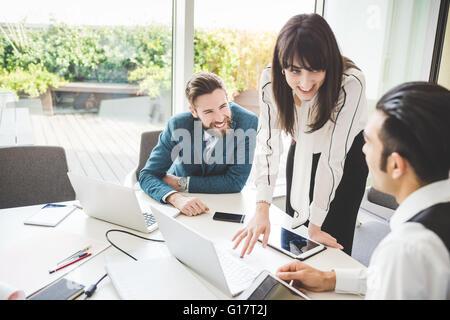 Joven Empresaria explicando a equipo en la mesa de juntas