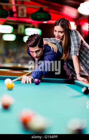 Joven apuesto hombre y mujer coquetear mientras juega billar