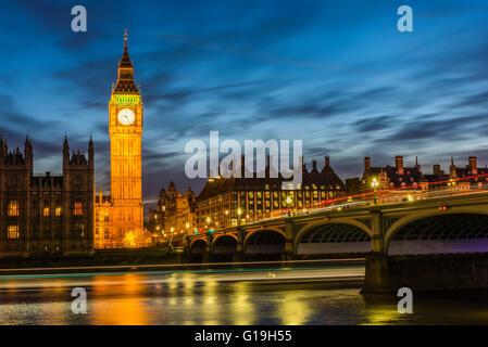 La larga exposición después del atardecer la captura de autobuses en Westminster Bridge y botes en el río Támesis, Londres, Reino Unido.