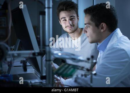 Los jóvenes ingenieros que trabajan en el laboratorio y utilizando un ordenador, impresora 3D en primer plano, el concepto de ciencia y tecnología