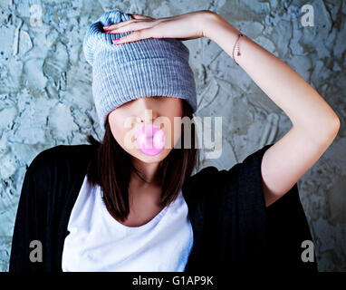 Adolescente con un chicle contra el viejo muro