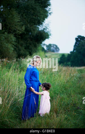 Madre e hija andando por el camino entre campos, tomados de las manos