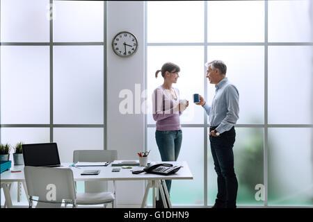 Alegre, trabajadores de oficina en la oficina, relajarse con un café y charlar juntos, ellos están de pie delante de la