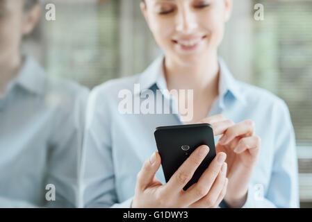 Hermosa mujer sonriente con un teléfono inteligente, apoyándose en una ventana y reflexionando sobre vidrio Foto de stock