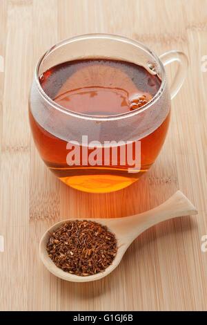 Taza con té de Rooibos Sudafricano y una cucharada de té secas