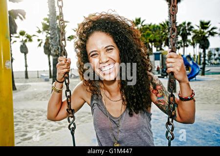 Raza mixta mujer sentada sobre swing en playa Foto de stock