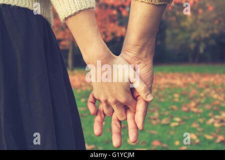 Cerrar en las manos de una pareja en el parque en otoño