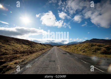 Nubes blancas mullidas e interminable camino abierto en la A832 en el extremo noroeste de Escocia, Reino Unido