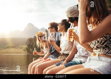 Retrato de los jóvenes, hombres y mujeres sentadas en jetty con cervezas. Los jóvenes hombres y mujeres disfrutando de un día en el lago.