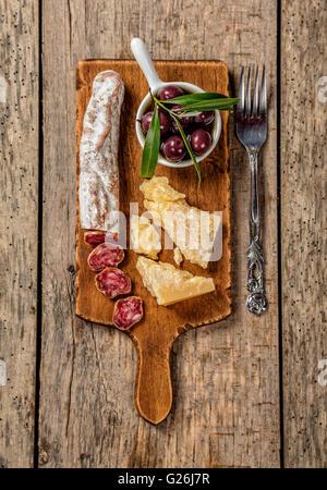 Diversos tipos de queso tradicional y la delicadeza adecuada para el vino, colocados en la tabla de cortar de madera, disparado desde un alto ángulo de visualización.