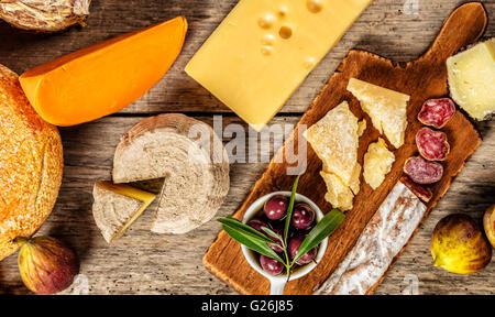 Diversos tipos de queso tradicional y la delicadeza adecuada para el vino, colocados sobre madera, disparado desde un alto ángulo de visualización.