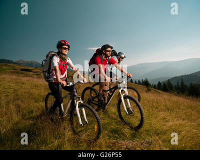 Los ciclistas de montaña en medio de un prado, mirando atentamente el hermoso paisaje