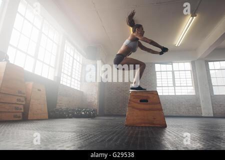 Vista lateral de ajuste de imagen joven haciendo un cuadro saltar el ejercicio. Mujer muscular haciendo un cuadro en cuclillas en la cruz montar gimnasio