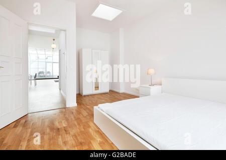 Conversión de Dach o espacio loft en Reichenberger Strasse, Kreuzberg. Dormitorio moderno de color blanco, con muebles y decoración minimalista. Las paredes blancas y suelos de madera. Vista del resto de loft abierto a través de la puerta del dormitorio