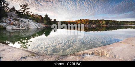 Rocas y árboles de otoño en la orilla del lago George, Killarney Provincial Park, Ontario, Canadá Foto de stock