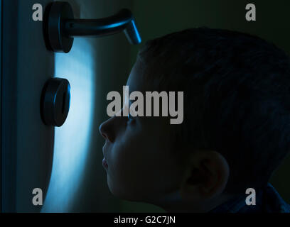 Niño en una habitación oscura, mirando en el resplandor de la linterna a través de una cerradura.