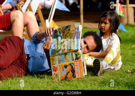 Hay Festival, Gales, Reino Unido - Mayo de 2016 - El primer fin de semana del Hay Festival un visitante tiene tiempo para mirar libros con un niño en el Festival el césped durante el sol de la tarde.